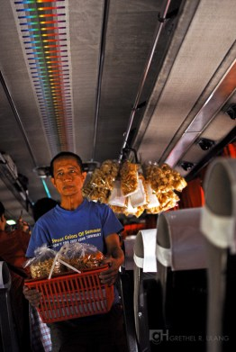 A vendor in the bus selling delicacies.