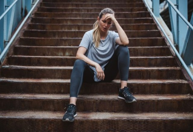 Woman sitting on stairs in exercise clothing-3 Ways to Break Out of a Running Slump