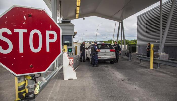Champlain, NY, border crossing with large stop sign where Customs and Border Protection seized money inspecting a vehicle.