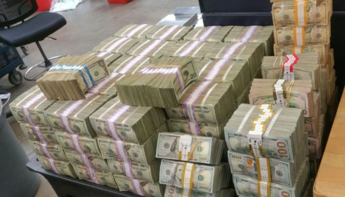 An image of $3M in crisp bills stacked high in a cube in bundles