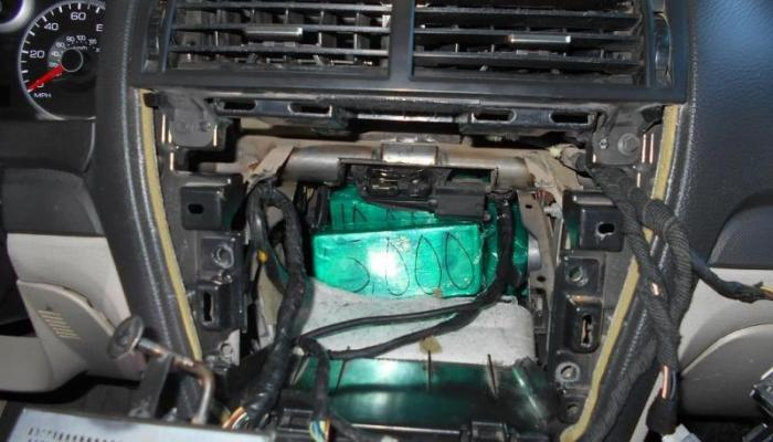 A picture of bulk cash from behind the stereo in the dashboard in a bulk cash smuggling seizure CBP officers removed