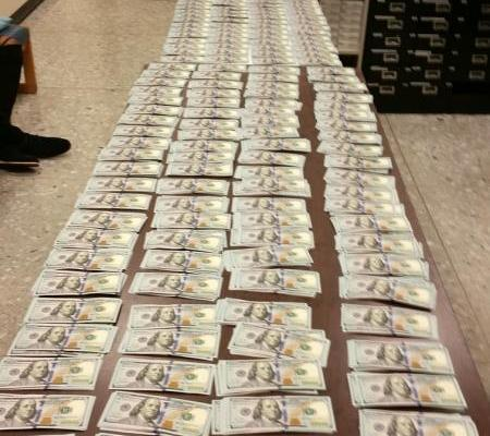 $150,000 laid out on a table at Dulles airport after the cash was seized by Customs