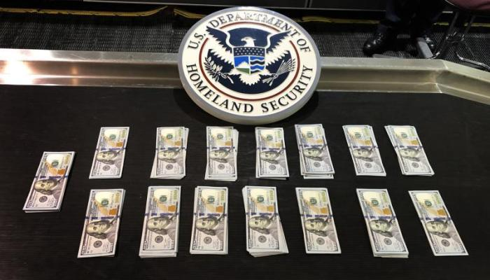 $20,000 in U.S. Currency stacked in piles after seizure by Customs at Boston Logan airport.