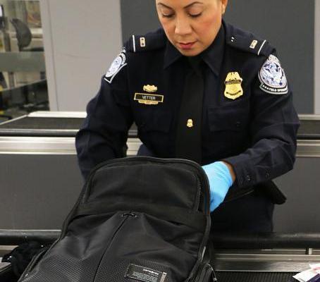 CBP officer inspecting traveler's backpack