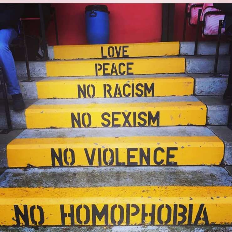 Whitehawks FC signage on the steps in the stand: Love, Peace, No Racism, No Sexism, No Violence, No Homophobia