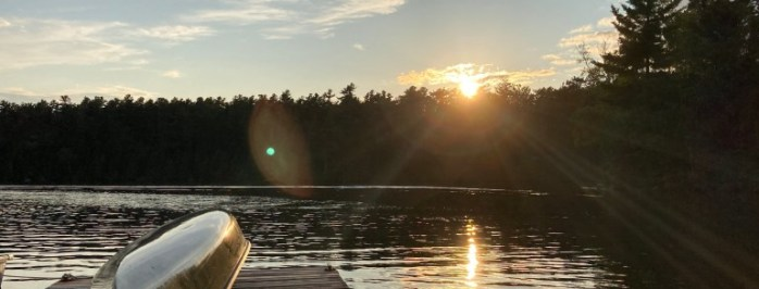 The sun is setting in the summer behind the trees on Lake Temagami with a canoe on the dock.