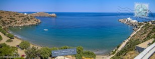 Blue sea in bay with beach and white monastery