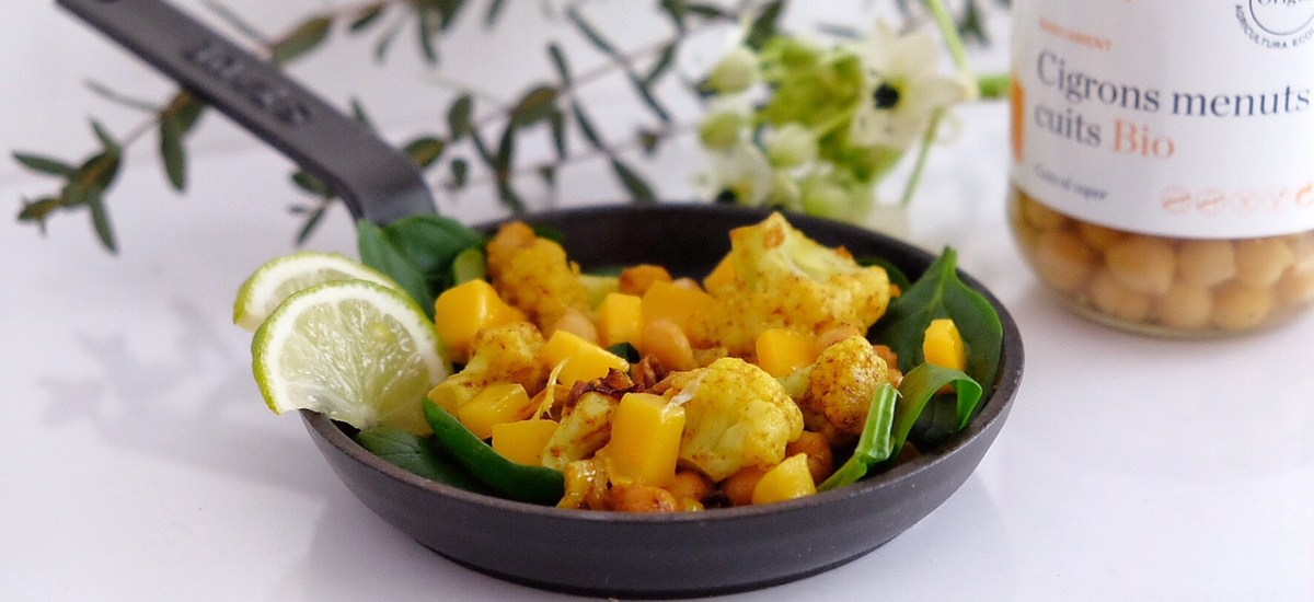Warm chickpeas and cauliflower salad with curry, raw spinach and mango