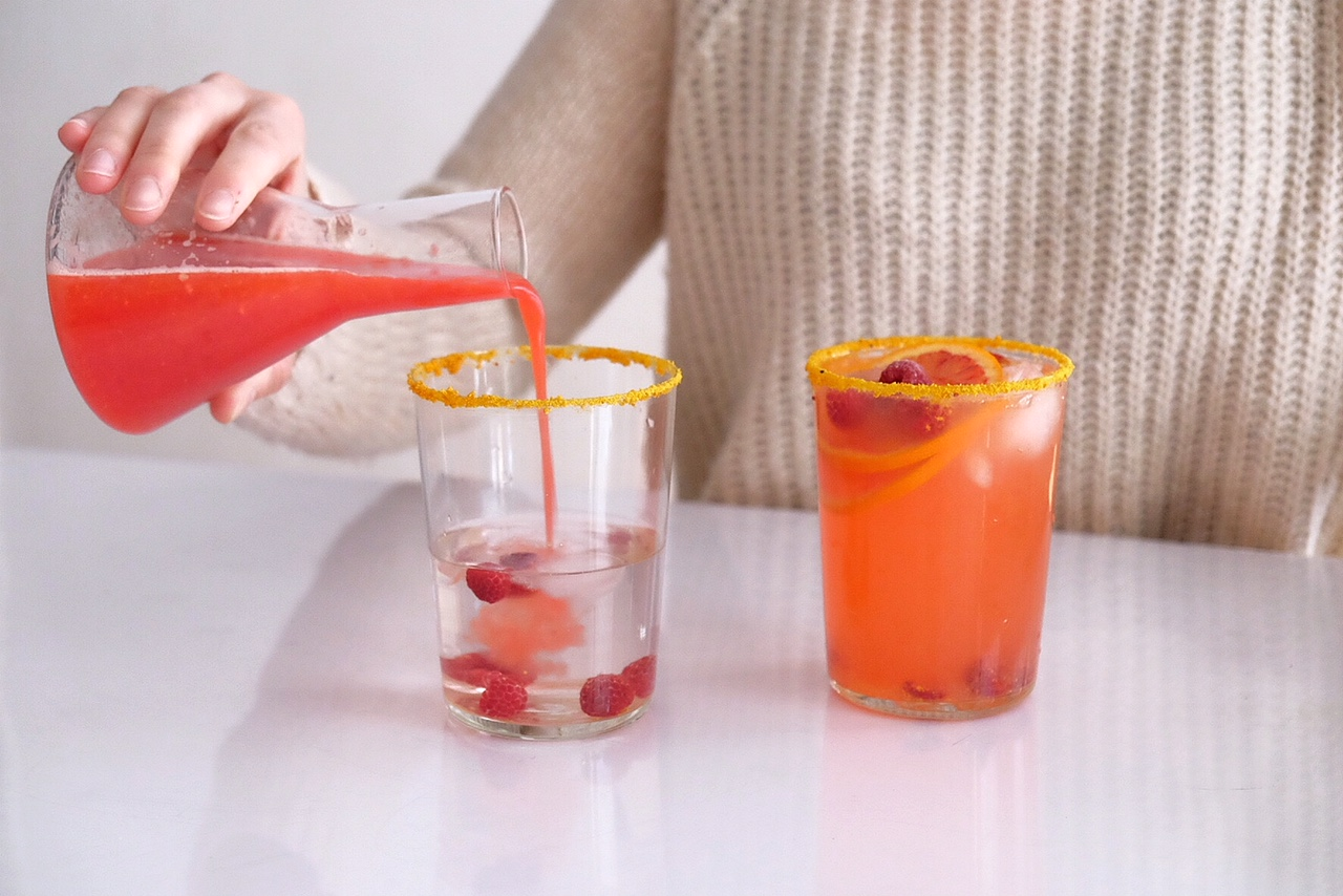 A refreshing lemonade with citrus fruits and raspberries