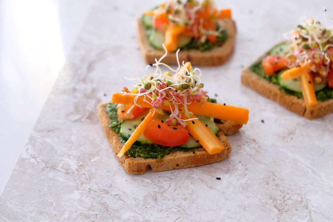 Toast with fresh pesto, raw vegetables and sprouted seeds