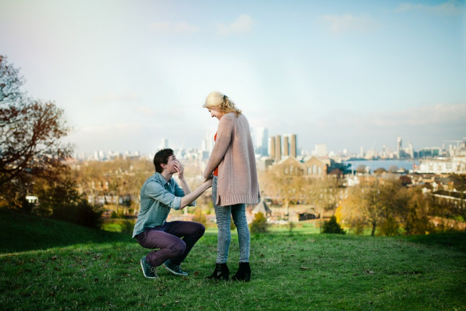 Man gets on his knees to propose to his fiance in Greenwich Park by London wedding and portrait photographer