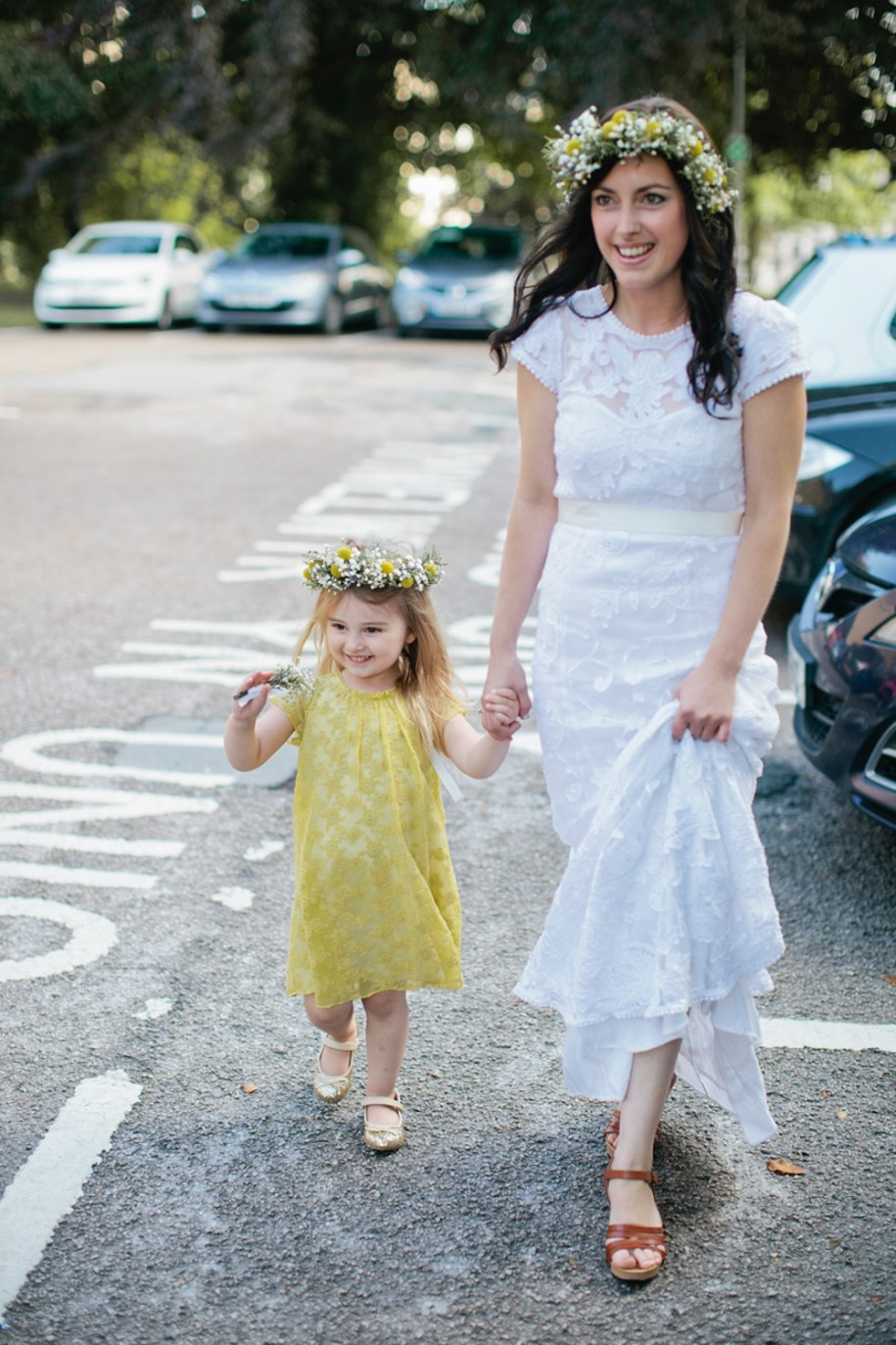 Bride and flower girl walking by Hawarden festival wedding photographer