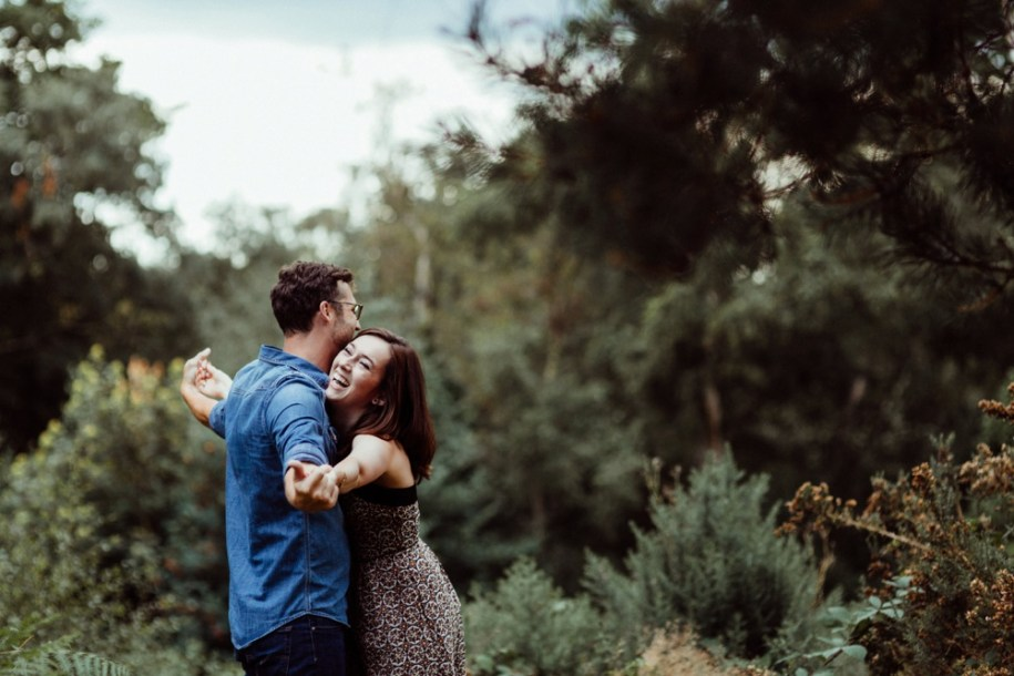couple laughing in London park for engagement shoot