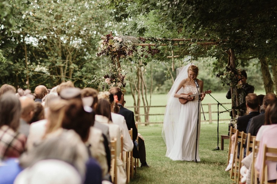 bride playing the ukulele during her outdoor wedding ceremony in Oxfordshire