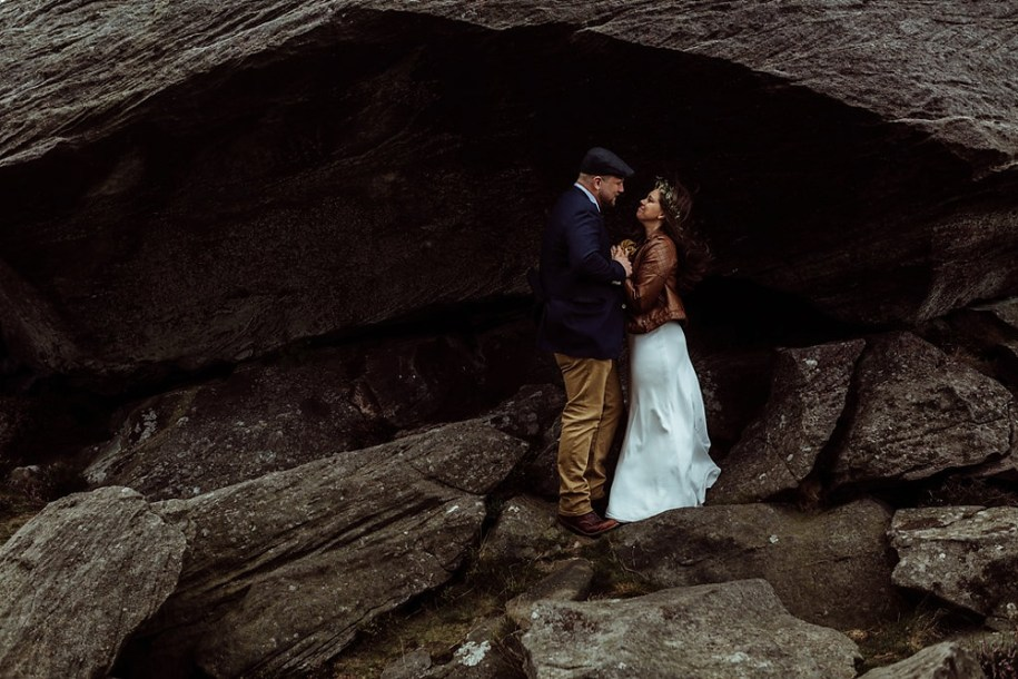 bride and groom under a big rock by Northumberland wedding photographers