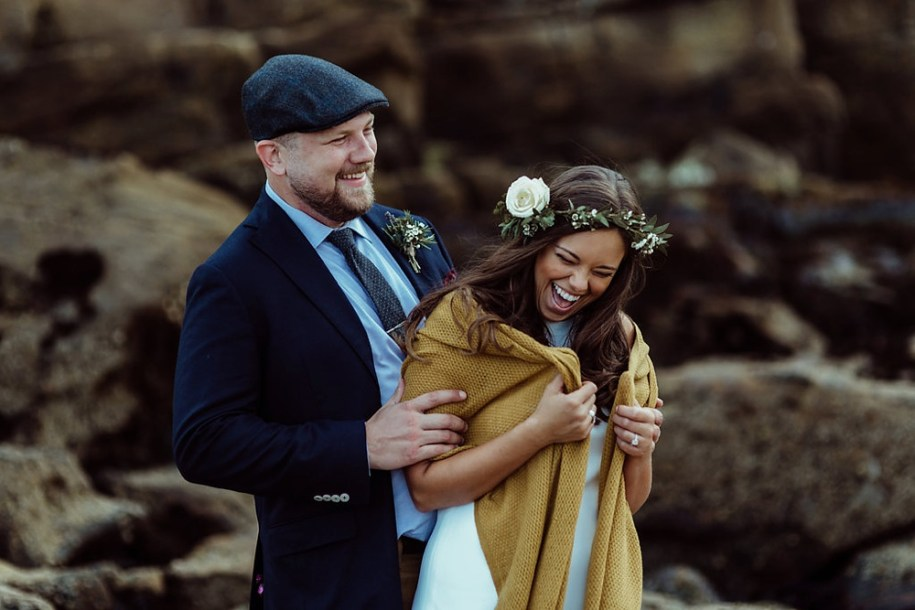 bride and groom laugh during portrait shoot in tynemouth beach side