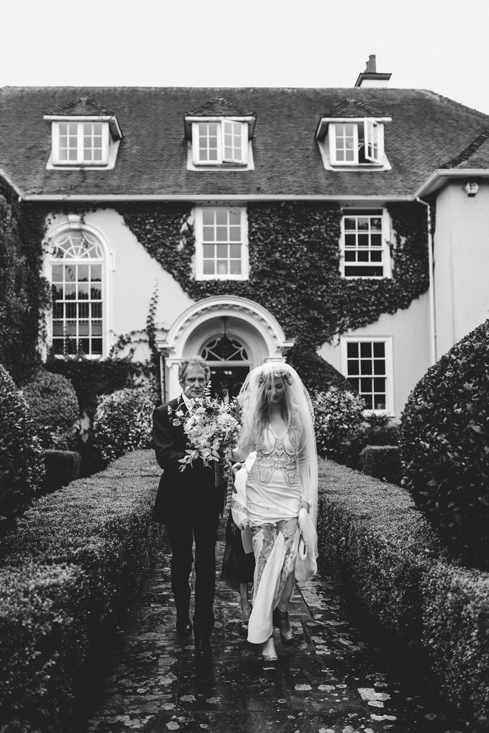 black and white image of bride and dad in front of their home in New Forest