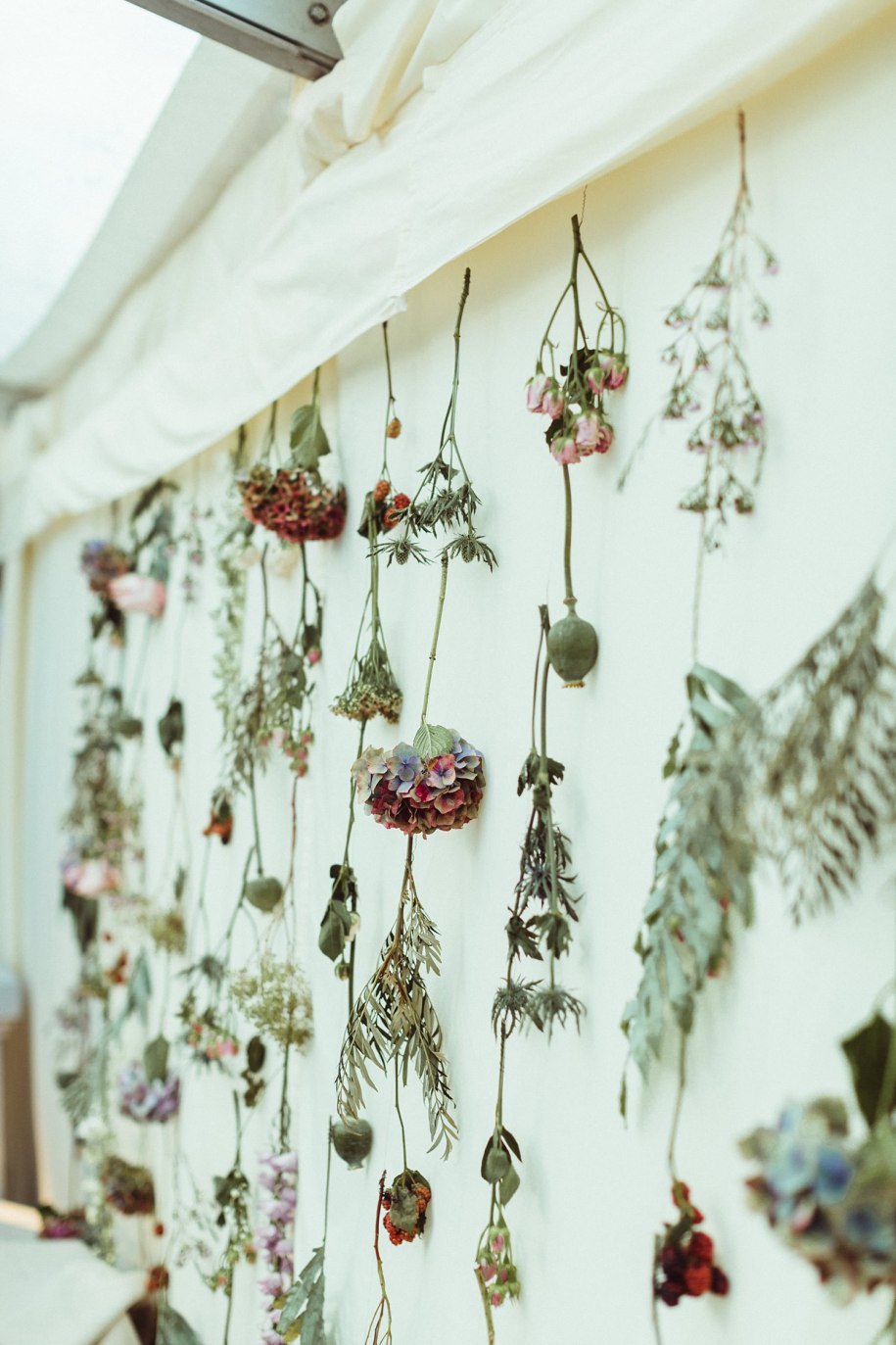 wedding flowers tied on the wall of a marquee at reception
