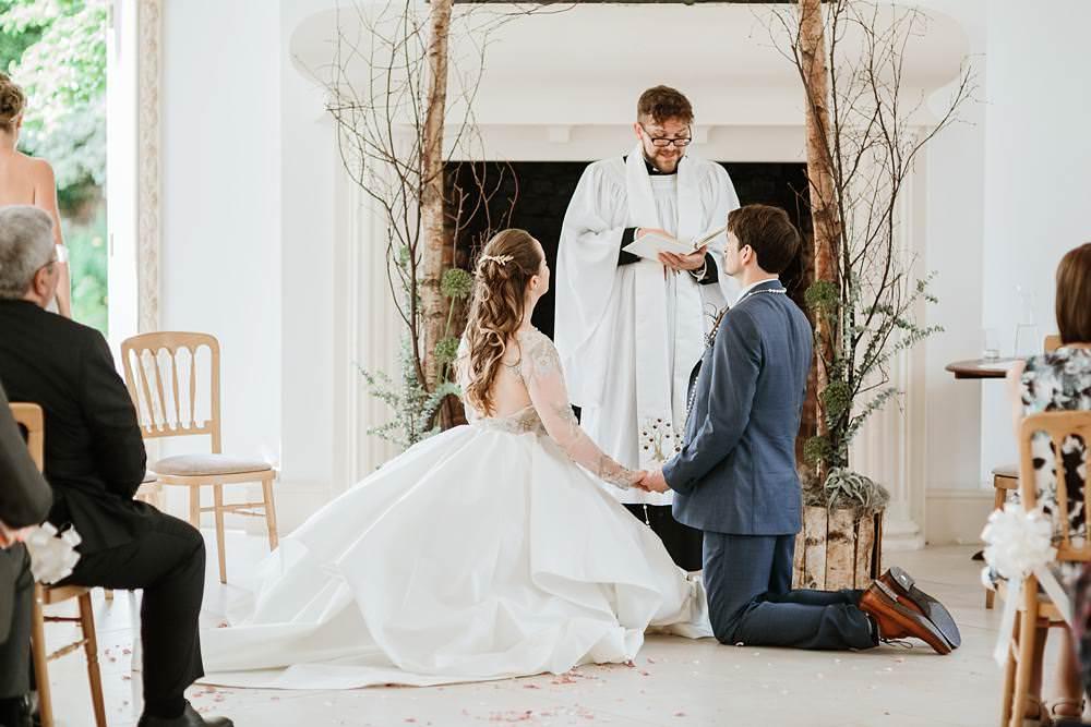 prayer over bride and groom during northbrook park wedding ceremony
