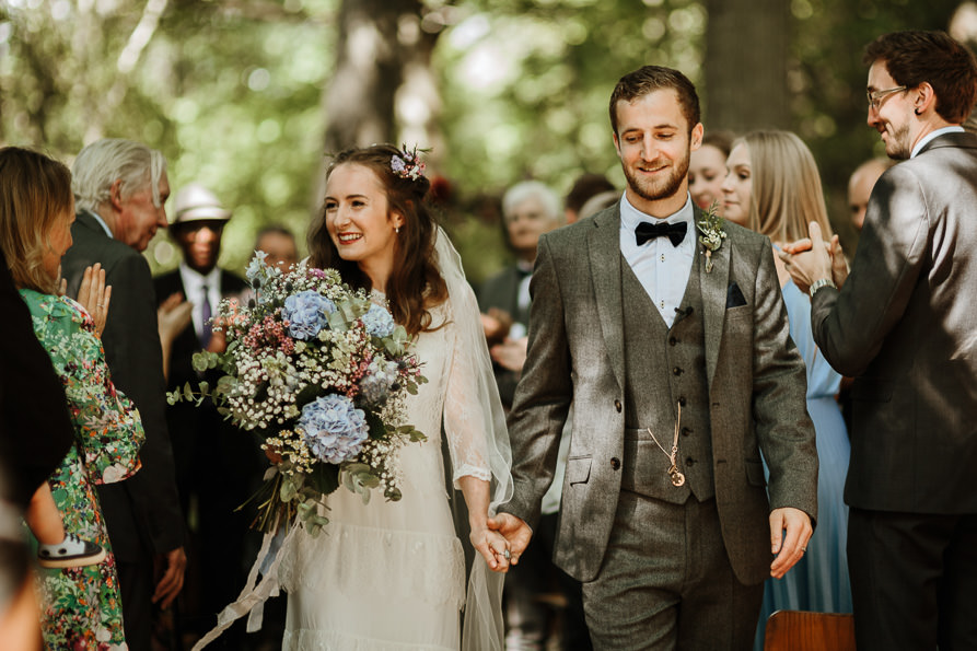 bride and groom walking down the aisle for their forest wedding ceremony