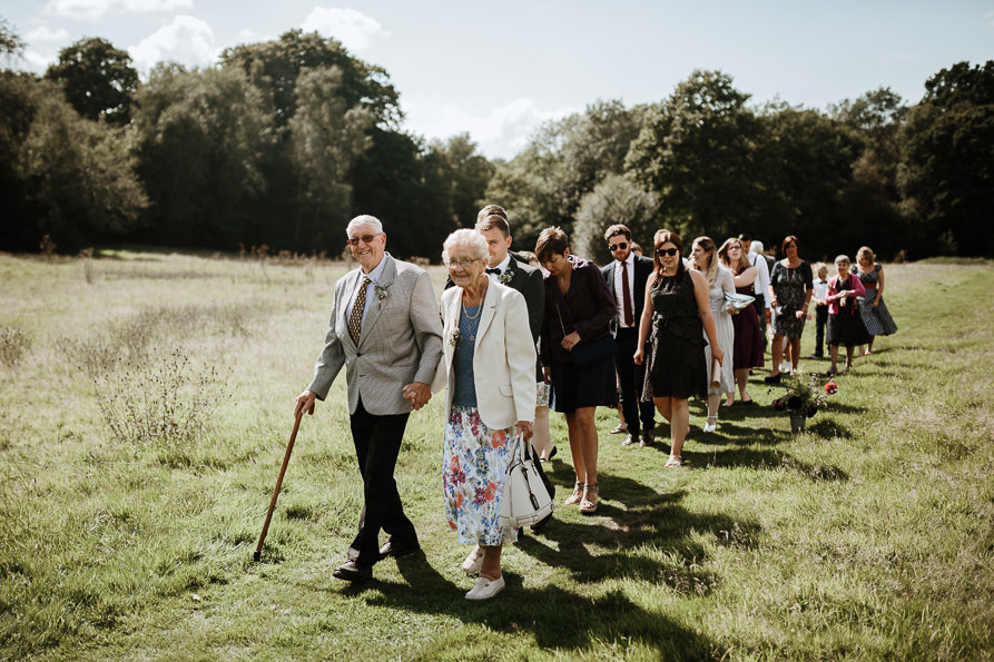 guests walking from forest wedding ceremony