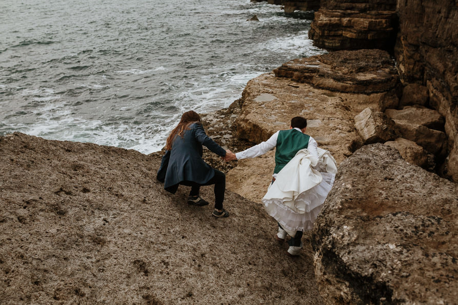 bride and groom on edge of coast at Portland Bill Dorset