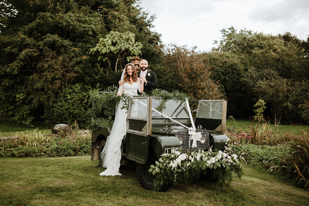 couple portraits in vintage landrover with flowers for dorset wedding