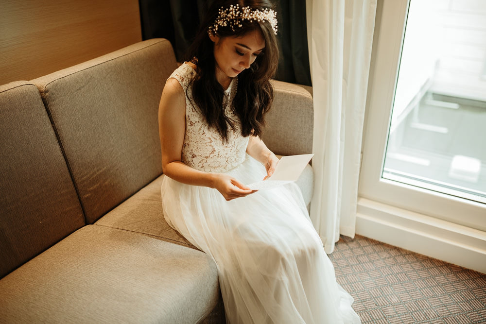 bride reading letter from the groom on the morning prep
