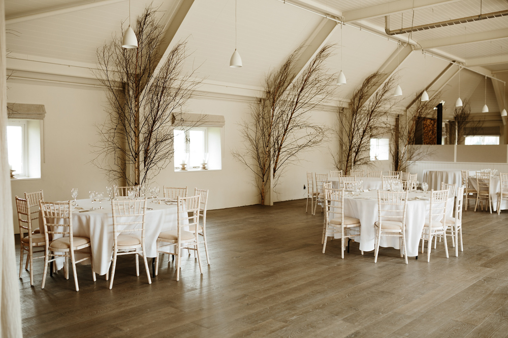 round tables with branches in the background for wedding reception at Lapstone Barn Cotswolds