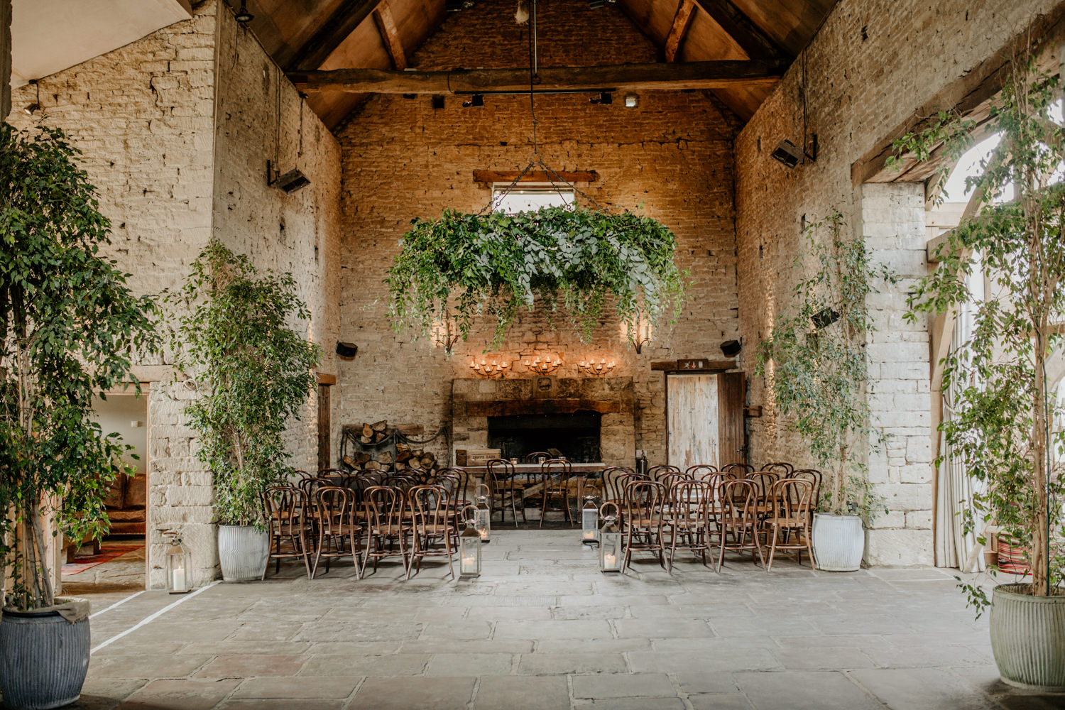 ceremony area inside Cripps Barn with wooden chairs and greenery in front of fireplace