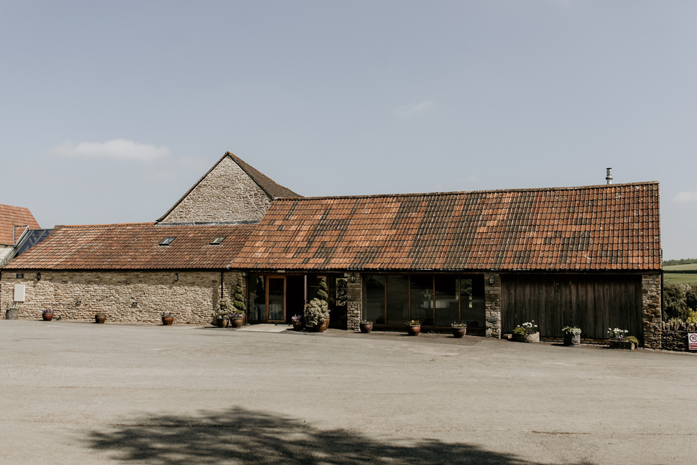 outside of The Kingscote Barn Wedding venue by Cotswolds Wedding Photographer
