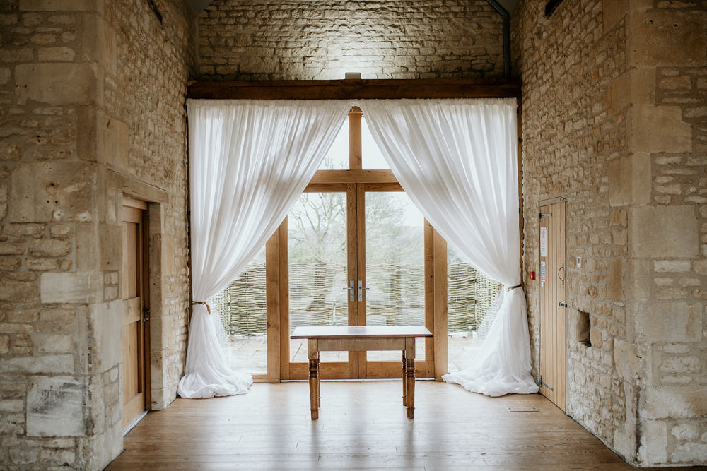 indoor ceremony area in the stone barn at The Barn at Upcote Cotswolds