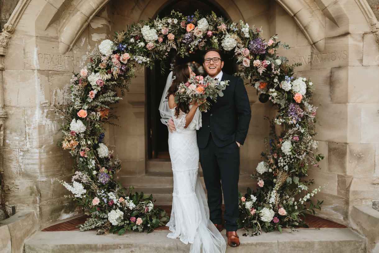 bride and groom in front of flower arch by wedding photographers Wales