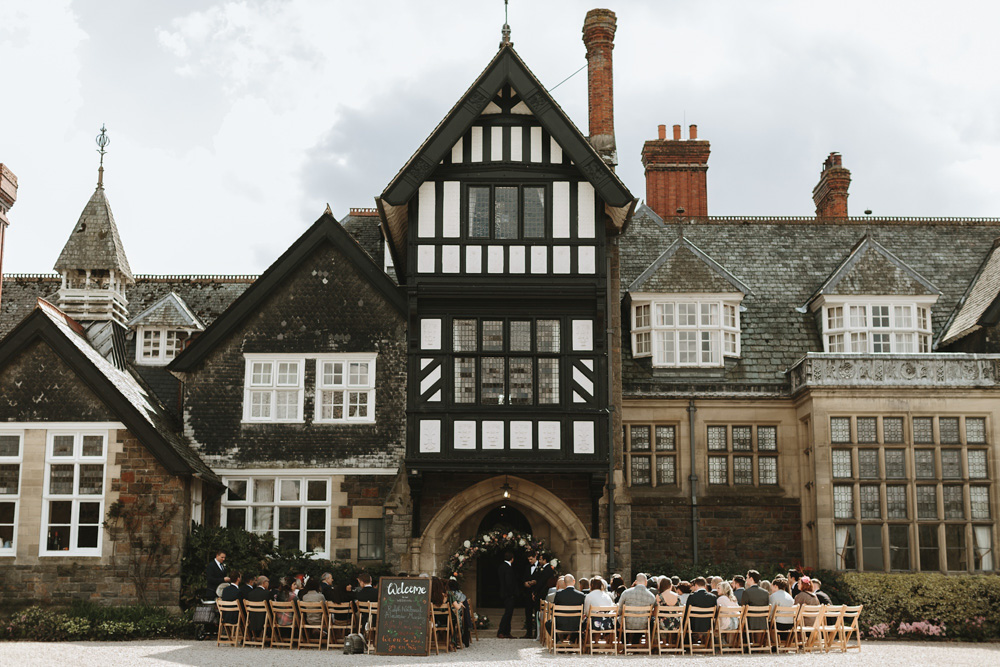 guests sitting outside Plas Dinam Country House for an outdoor wedding ceremony