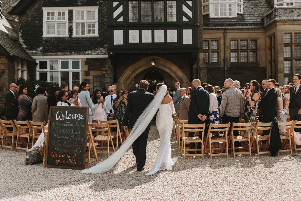 bride and dad walking towards the outdoor ceremony at Plas Dinam Country House