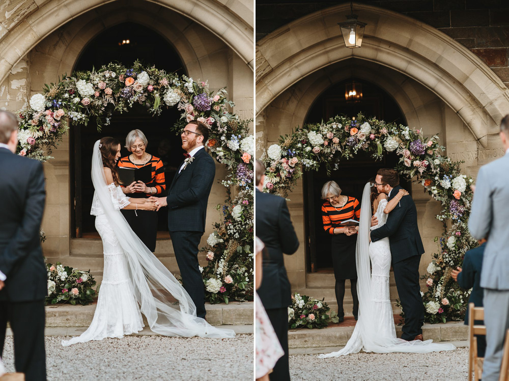 bride and groom vows in front of a flower arch at plas dinam country house in Wales