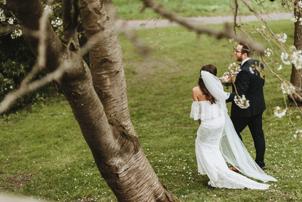 bride and groom walking on field during portrait photo shoot