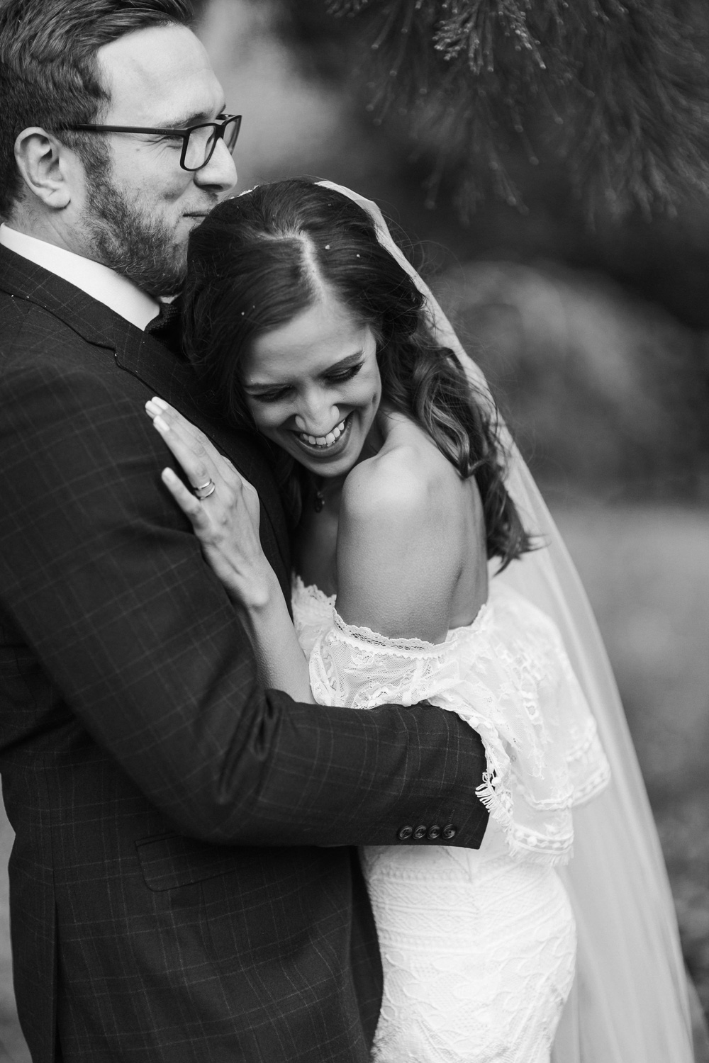 black and white image of bride and groom hug during their plas dinam country house portrait session