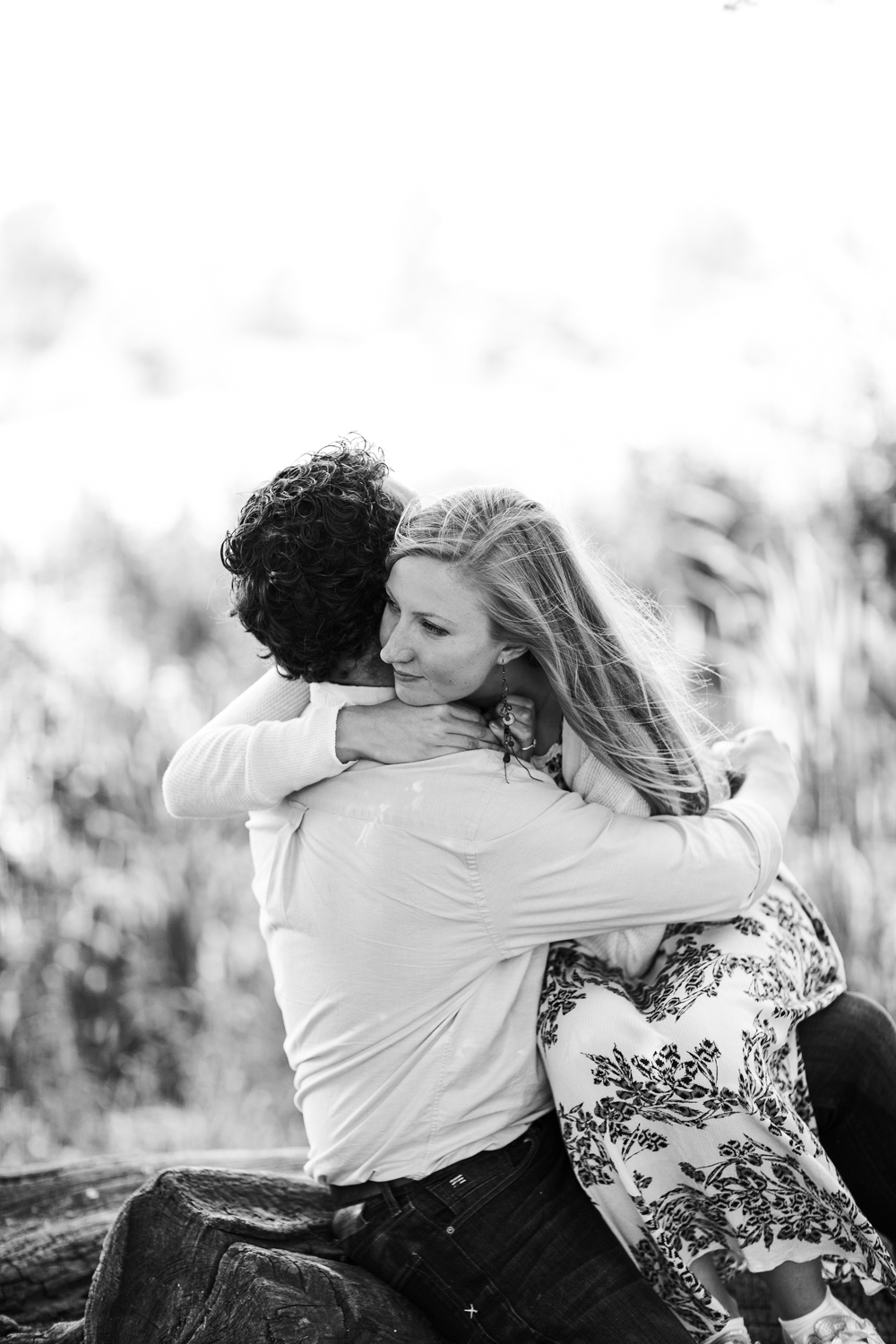 black and white image of couple hugging on a log in the park in Oxford city