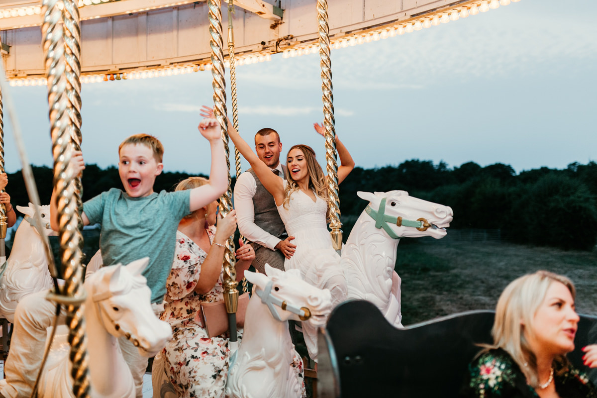 bride and groom on a horse for a carousel ride at preston court wedding venue by Canterbury wedding photographers