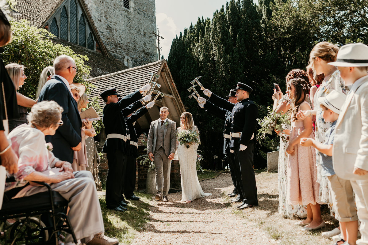 bride and groom walking through tunnel made by firemen by Canterbury wedding photographers