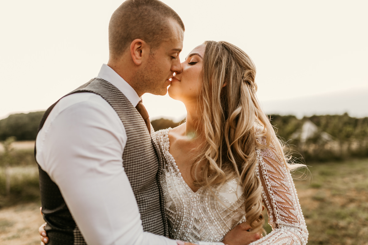 bride and groom kissing during the wedding couple session at preston court wedding venue by Canterbury wedding photographers
