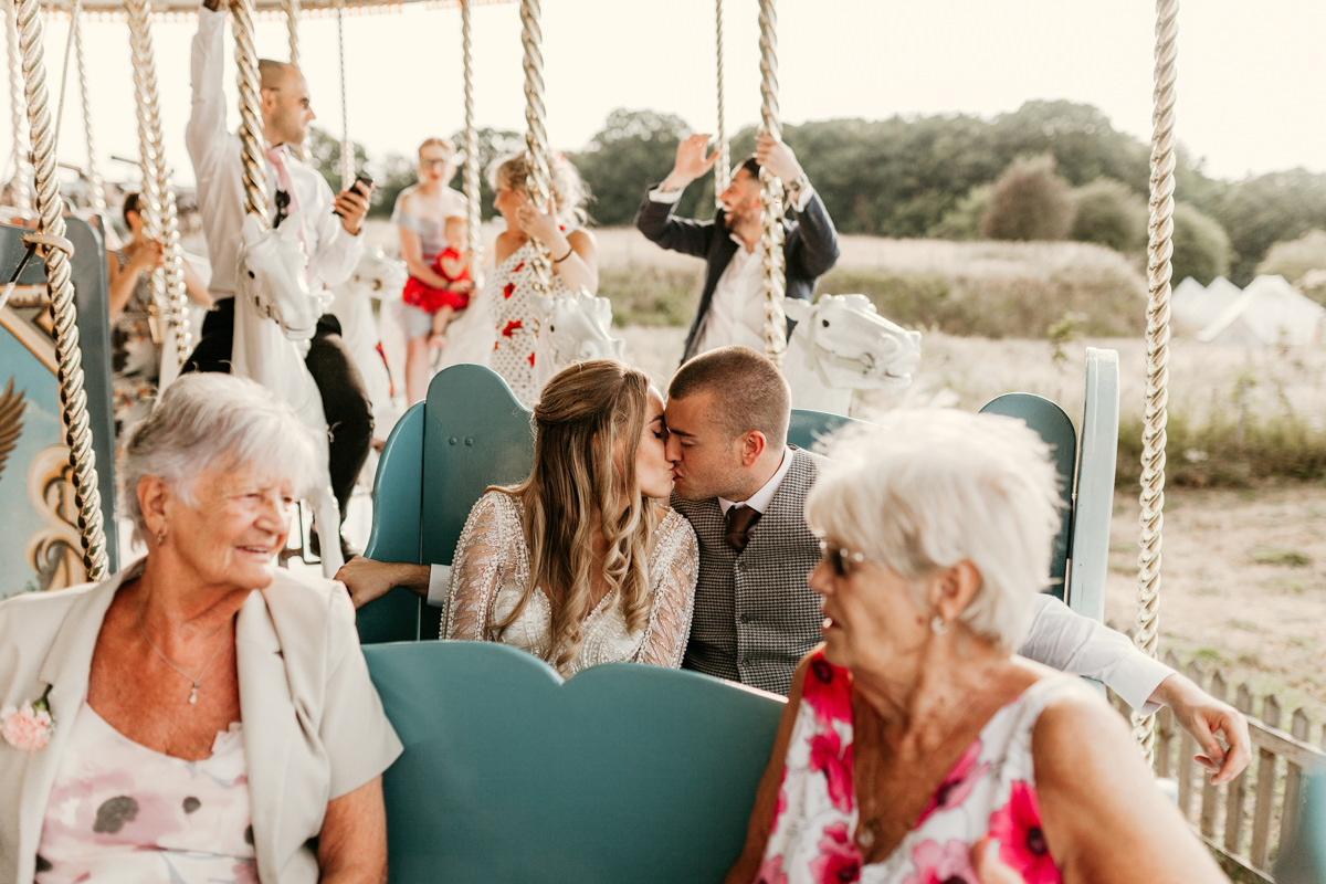 bride and groom kiss on carousel at preston court wedding venue by Canterbury wedding photographers