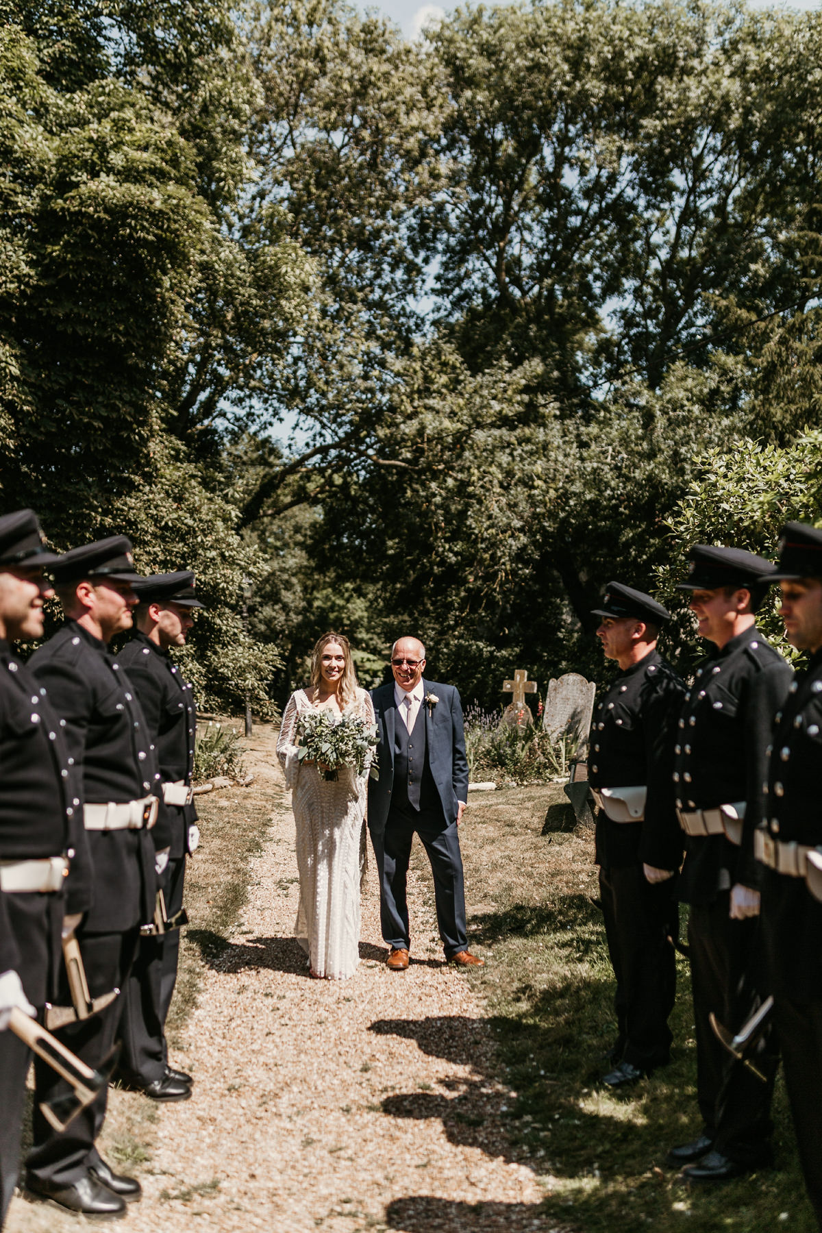 bride and father walking though tunnel made by firemen before the church wedding ceremony Canterbury
