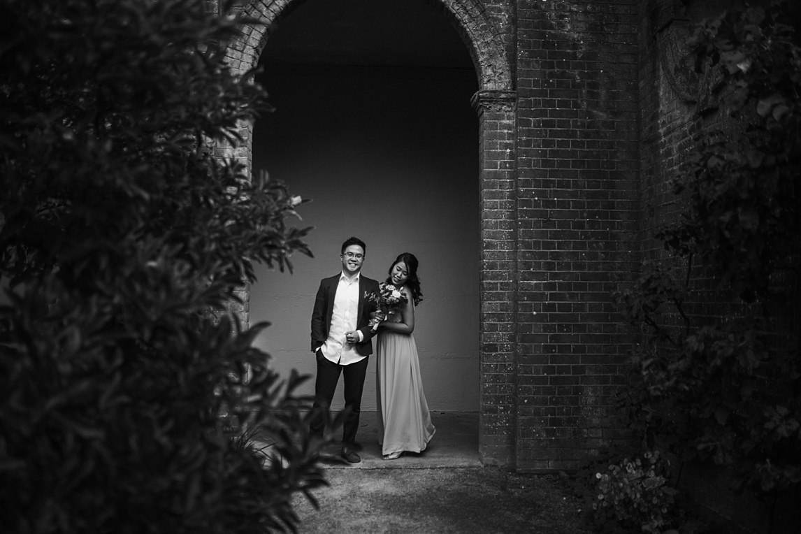 black and white image of engagement portrait under the arch at PErgola hill gardens hampstead heath