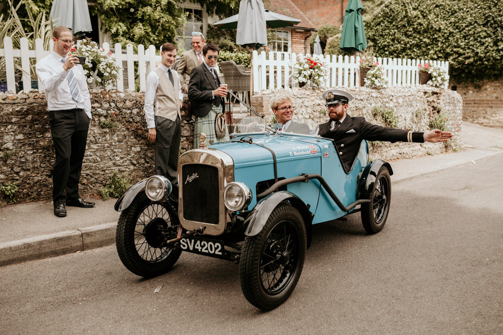 groom and groomsmen driving a vintage car for his The Kennels Goodwood wedding
