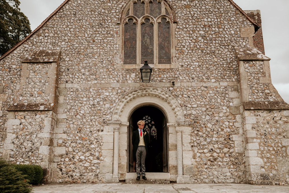 groom waiting in church doorway for guests at The Kennels Goodwood wedding