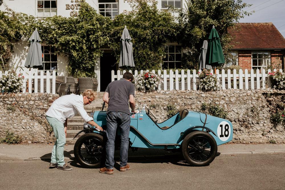 groom and groomsmen polishing a Austin 7 Ulster , the wedding car