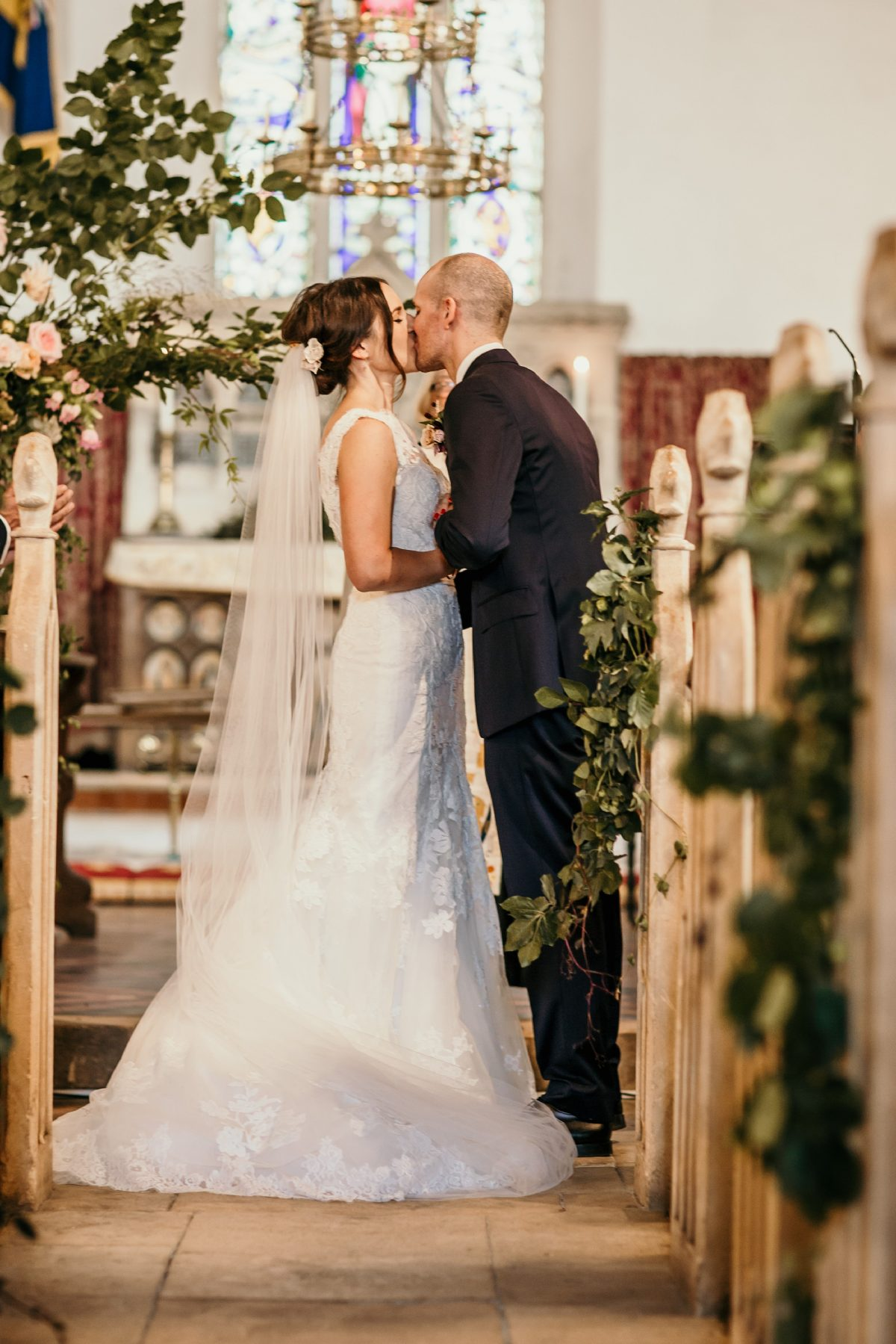bride and groom first kiss at Merriscourt Barn Wedding venue by Cotswolds wedding photographer