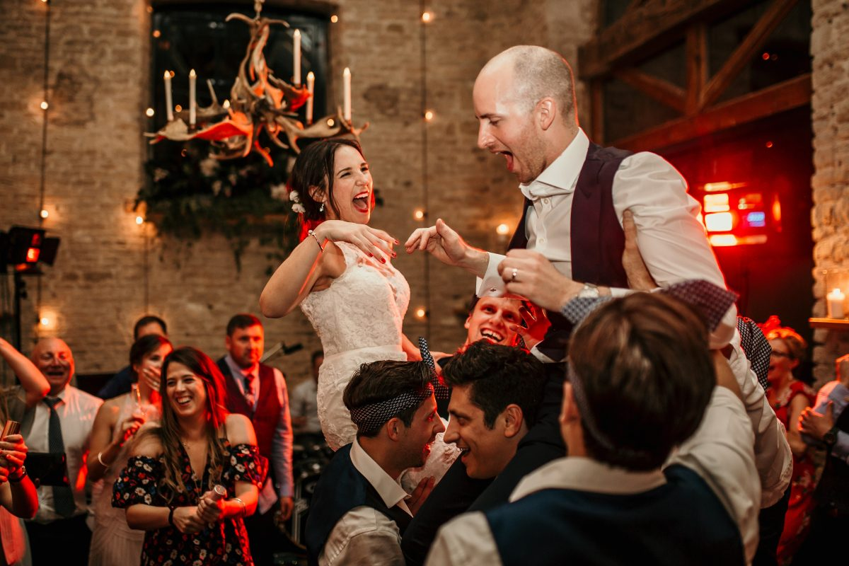 bride and groom on the groomsmen shoulders during the wedding party at Merriscourt Barn Wedding venue by Cotswolds wedding photographer
